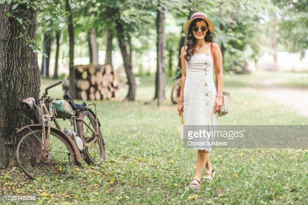 old fashioned woman near retro motorcycle - metallic dress stock pictures, royalty-free photos & images