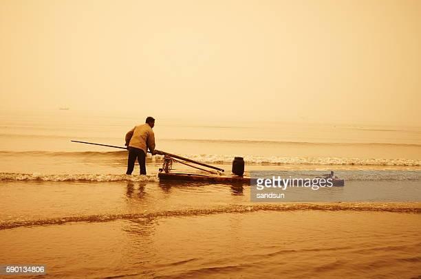 Vieux pêcheur sur un radeau de la mer Jaune.