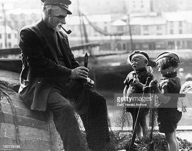 'A old fisherman sits on an upturned boat 1936 A old fisherman sits on an upturned boat in the harbour smoking his pipe and chatting to two young...