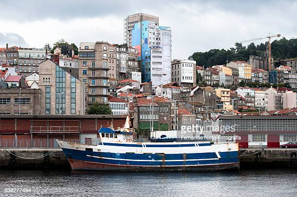 old fishing boat docked at the pier next to the buildings of the city - vigo stock pictures, royalty-free photos & images