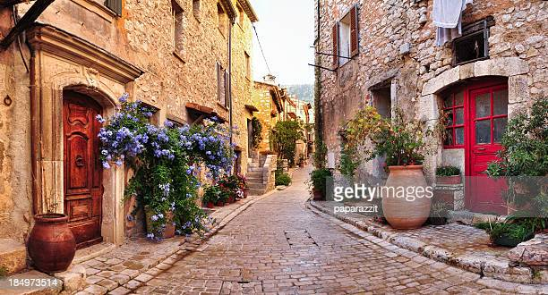 old french village houses and cobblestone street - franse cultuur stockfoto's en -beelden