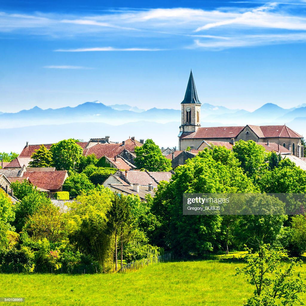 Old French village in countryside with Alps mountains in summer : Stock Photo