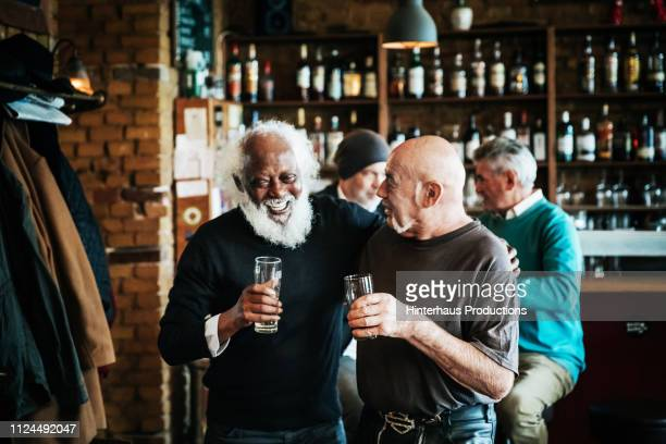 old friends catching up at craft beer bar - 70 79 years stock pictures, royalty-free photos & images