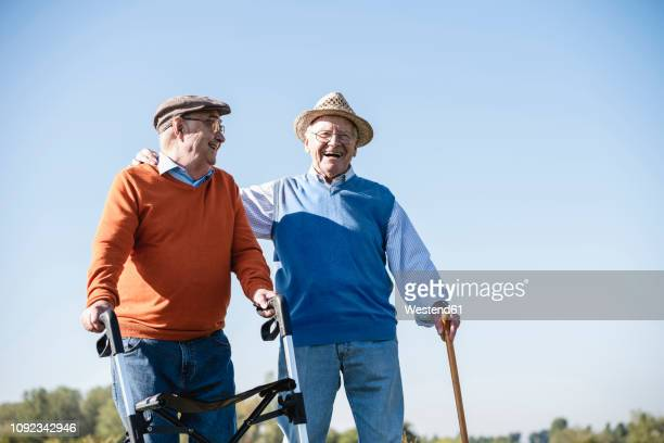 old friends taking a stroll in the fields with walking stick and wheeled walker, talking about old times - fragility stock pictures, royalty-free photos & images