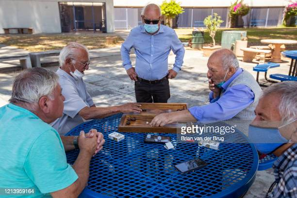 Old friends who share Iranian heritage and Assyrian language, while wearing masks, or not, play backgammon while enjoying each others company at...