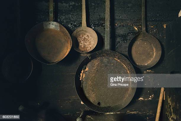 Old frying pans hanging on a wall.