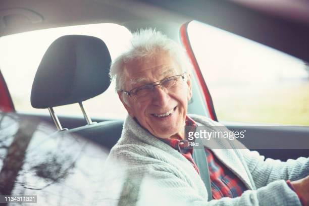 Old gentleman drives car and laughs at the camera