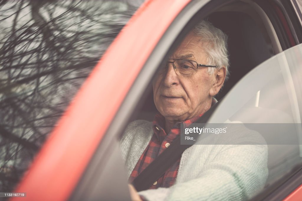 Old gentleman drives car : Stock Photo