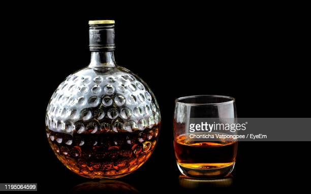 old glass bottle of scotch whiskey on black background - scotch whiskey stock pictures, royalty-free photos & images