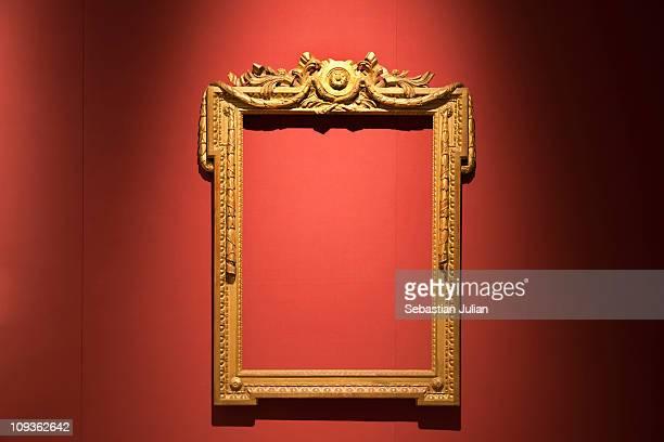 old golden empty frame against red silk wallpaper