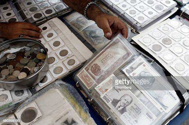 Old Greek drachma and collectible currencies sit on display at a street vendors's stall at the Monastiraki flea market in Athens Greece on Saturday...