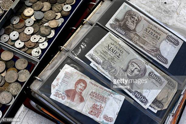 Old Greek drachma coins and banknotes sit for sale at a street vendor's stall in Athens Greece on Thursday May 28 2015 A failure to reach an...