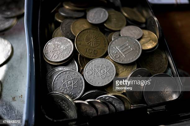Old Greek drachma currency coins sit in a box at an antique dealer's store in Thessaloniki Greece on Wednesday May 27 2015 Greek banks forced into a...
