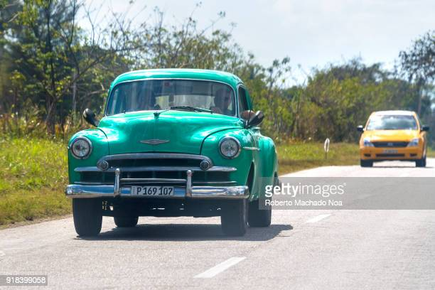 Old green Chevrolet car driving on a rural road The vehicle is followed by a modern taxi