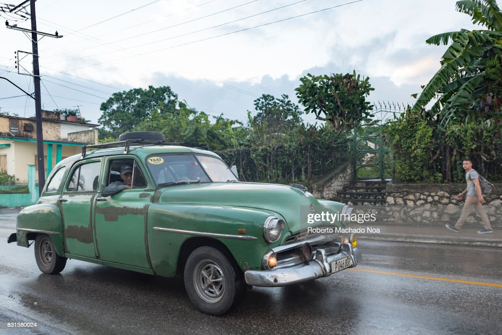 Old green Chevrolet car working as private taxi on a rain ...