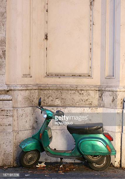 Old green scooter parked in Rome, Italy