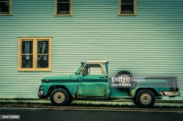 old green truck against green building - small town america stock pictures, royalty-free photos & images