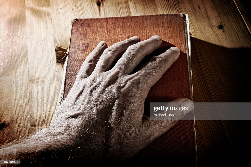Old Hand on Book : Stock Photo