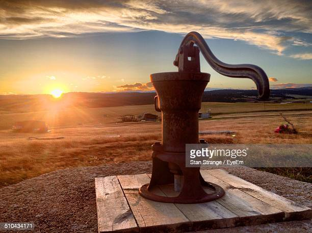 Old hand water pump at sunset
