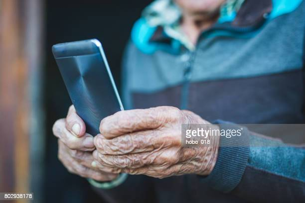 Old hands hold smart phone