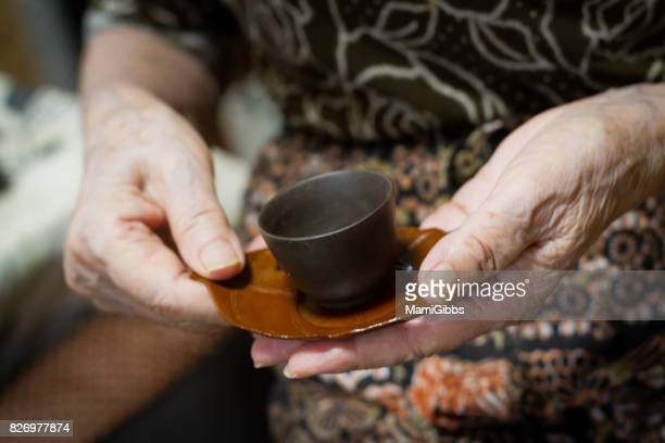 old hands holding asian tea - kanagawa prefecture stock pictures, royalty-free photos & images