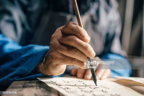 Old hands of man writing Chinese script -