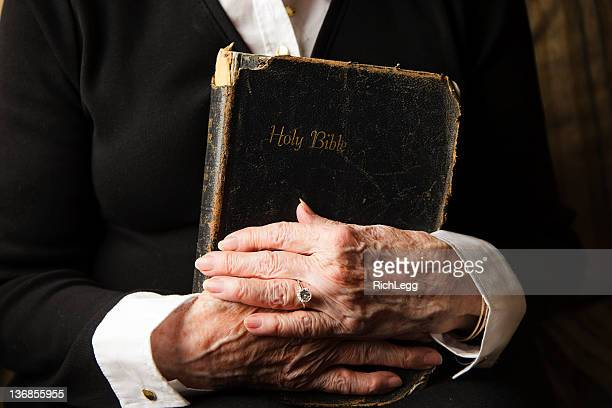 old hands on an antique bible - bible stock pictures, royalty-free photos & images