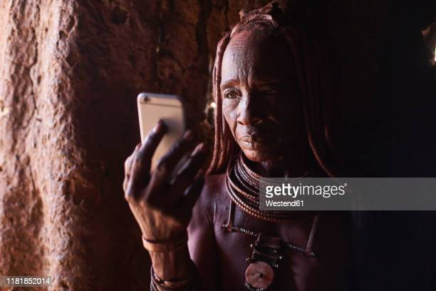 old himba woman checking her smartphone, oncocua, angola - himba foto e immagini stock