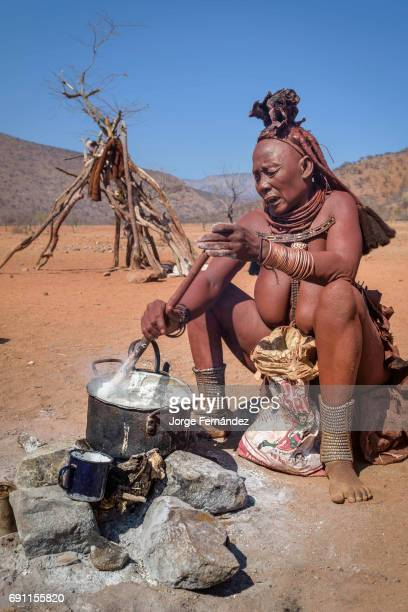 Old Himba woman cooking on the fire a traditional african meal made out of maize flour and water