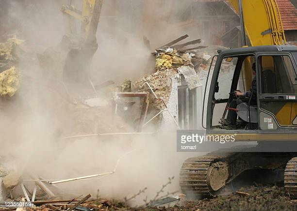 Old house being demolished by a yellow excavator