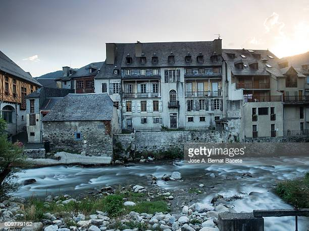 Old house facing a river running through the village in france  Pyrenees, (Arreau)