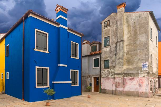 Old house for sale next to a renovated blue house, Burano, Veneto, Italy