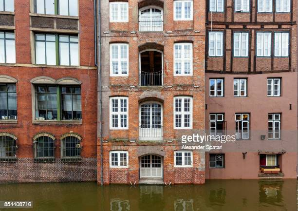 old houses along the canal during high tide in hamburg, germany - altbau fassade stock-fotos und bilder