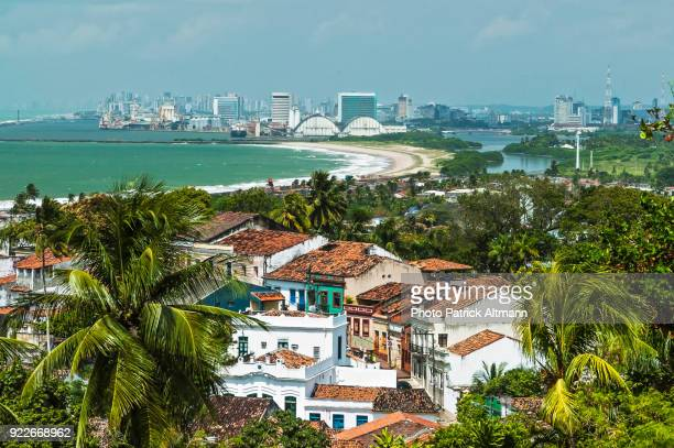 old houses on unesco world heritage site in a tropical environment surrounded by palm trees. in contrast with a modern city on seaside that appears in the background. olinda, pernambuco, brazil - recife stock pictures, royalty-free photos & images