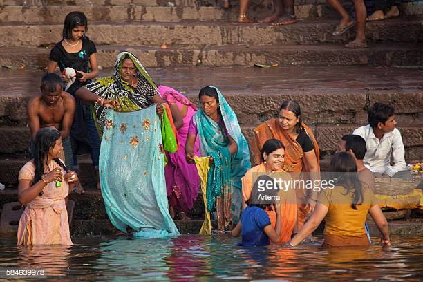 Old Indian women bathing in polluted water of the Ganges river at Varanasi Uttar Pradesh India