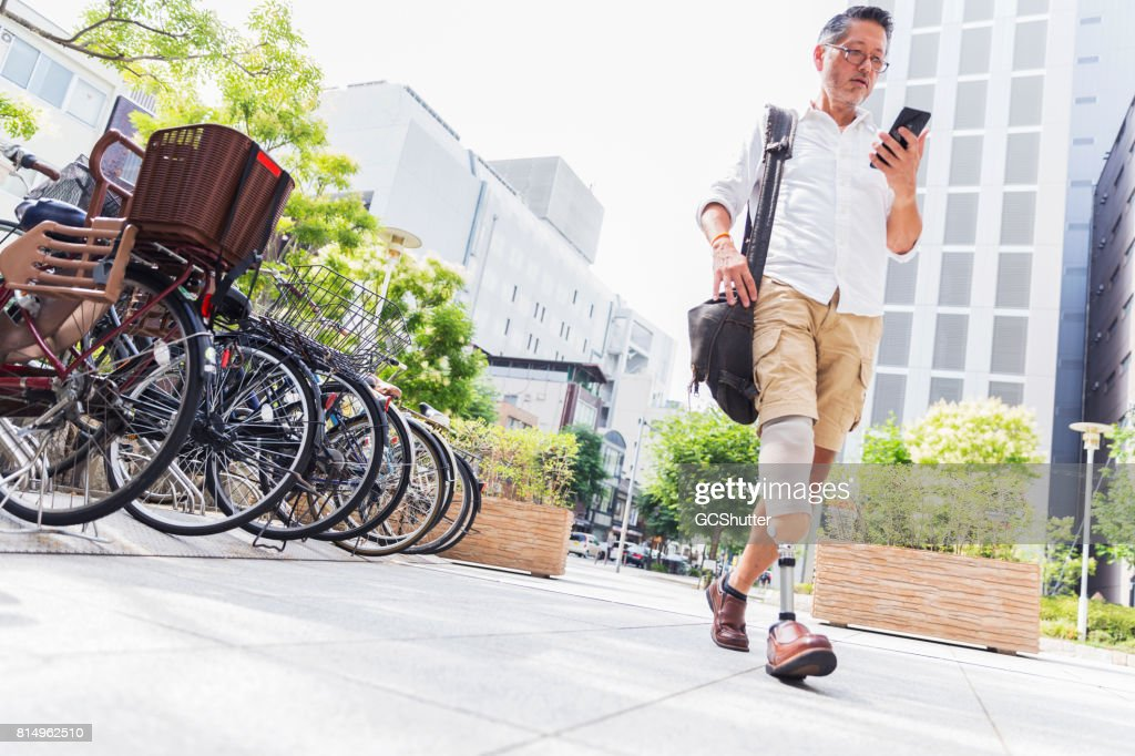 Old Japanese man walking in downtown while using his instant messaging app on a smart phone : Stock Photo