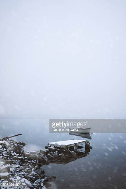 Old jetty and boat on a snowy day