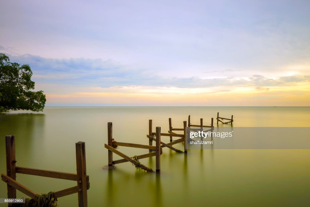 old jetty on the still water at Port Dickson, Malaysia stretches towards to horizon : Stock Photo