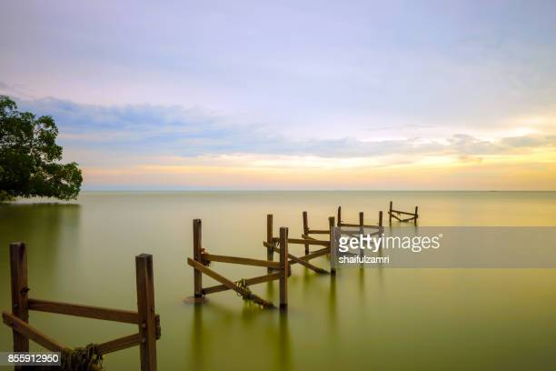 old jetty on the still water at Port Dickson, Malaysia stretches towards to horizon