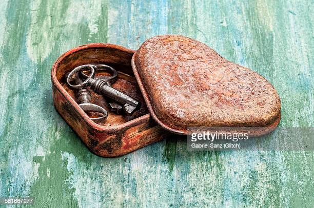 old keys in a box of heart-shaped metal - rust colored stock photos and pictures