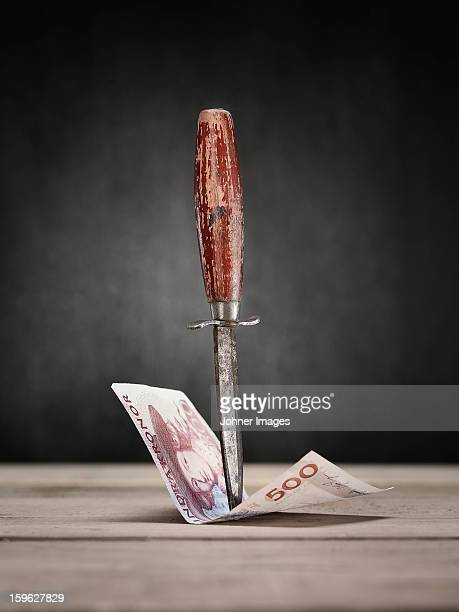 Old knife hitting banknote