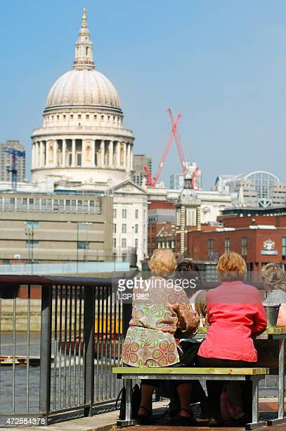 old ladies on a bench. london city background. - monument station london stock photos and pictures