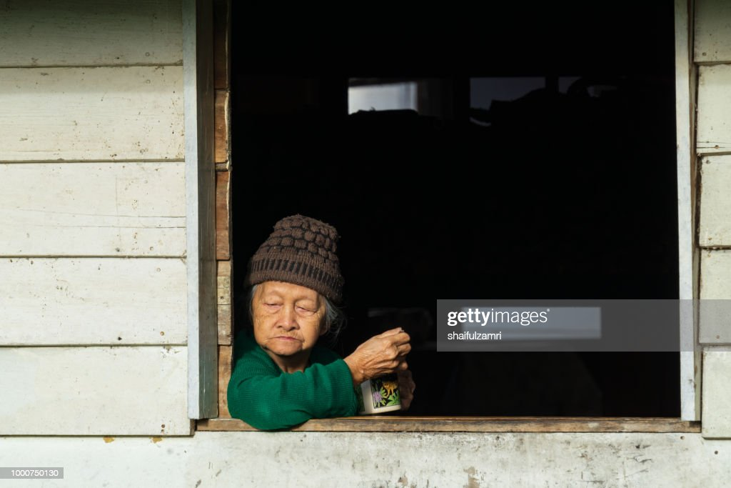 Old lady from Penan's tribe enjoying evening moment at Bario. : Stock Photo