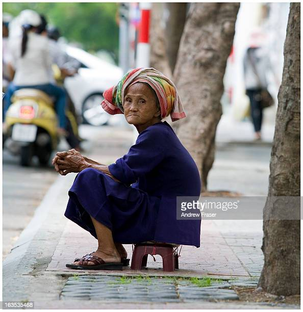 CONTENT] Old lady in a headscarf and sandals sitting on tiny stool Saigon Ho Chi Minh City Vietnam 2010