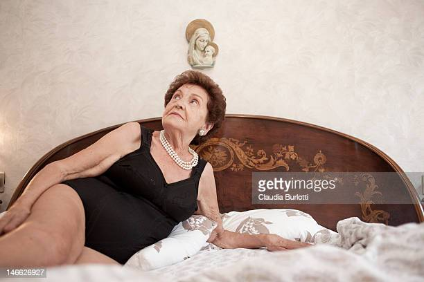 old lady in bodysuit laying in bed - old woman stock photos and pictures