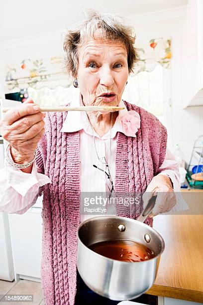 Old lady in kitchen lifts saucepan and tastes from spoon