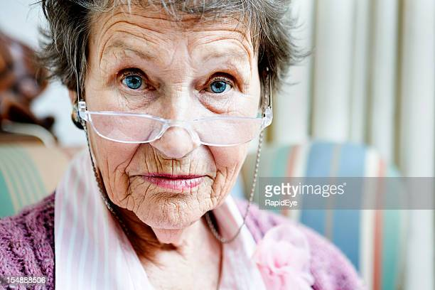 Old lady looks over spectacles, disapproving, eyebrows raised