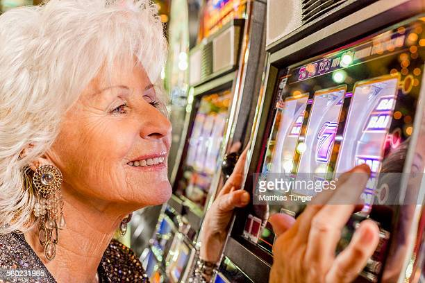 Old lady playing the slot machine