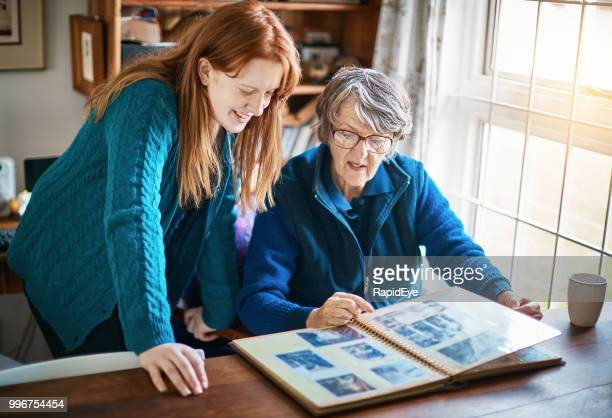 old lady shows her smiling granddaughter the family photo album - grandmother photos stock pictures, royalty-free photos & images