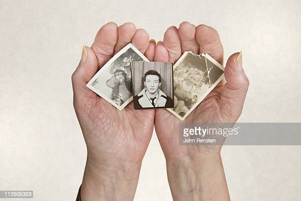 old lady's hands holding old photos